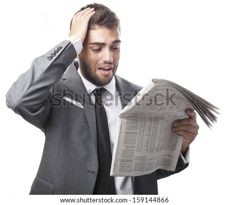 young scared business man reading a newspaper isolated on white - stock photo