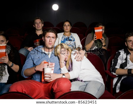 Young scared couple at the movie theater - stock photo