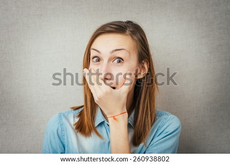 Young scared woman covering the mouth.cute girl embarrassed - stock photo