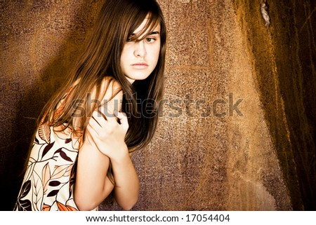 Young scared woman over grunge background - stock photo