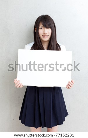 young school girl holding empty white board