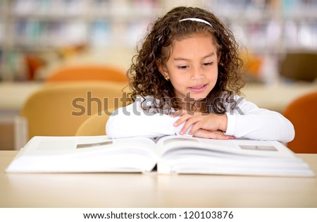 Young school girl reading a book at the library - stock photo