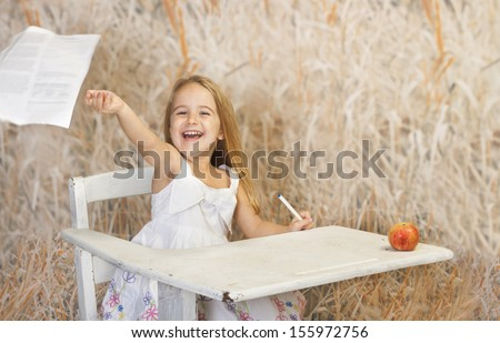 Young school girl throwing  away her homework paper , she has a big smile. - stock photo
