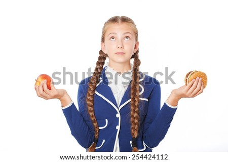 Young school girl trying to choose between apple and hamburger. Isolated on white background. Concept for healthy eating at school - stock photo