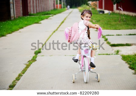 Young school girl with backpack rides her pink bike to school - stock photo