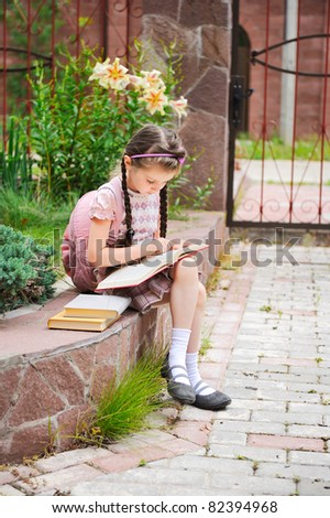 Young school girl with pink backpack sits reading the book - stock photo