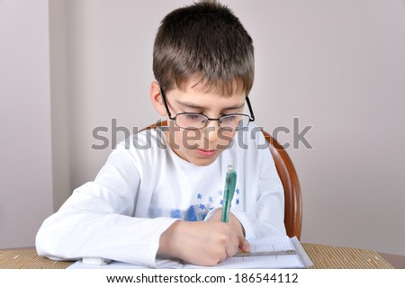 Young schoolboy doing his homework at home - stock photo