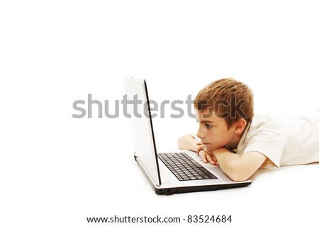 Young schoolboy is lying on floor with a laptop, isolated on white - stock photo