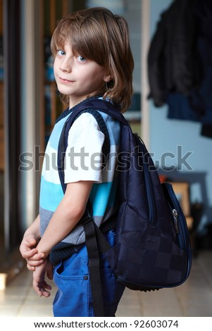 Young schoolboy with his backpack ready to go to school - stock photo