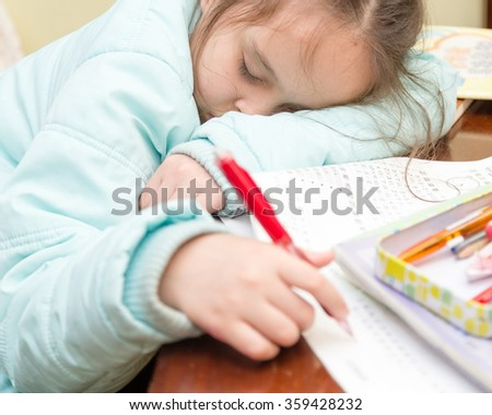 Young schoolgirl falling asleep while doing her homework - stock photo