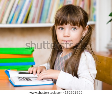 Young schoolgirl reading a book. looking at camera - stock photo
