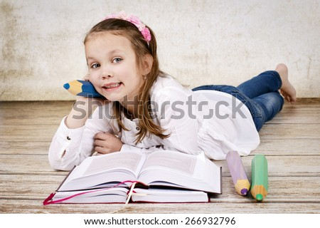 Young schoolgirl with books and pencils - stock photo
