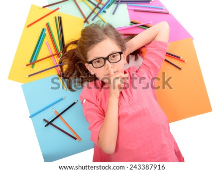 young schoolgirl with glasses lying on the floor amid of colored pencils - stock photo