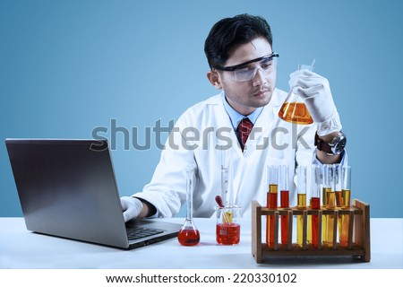 Young scientist doing experiment with chemical fluid and laptop computer in laboratory