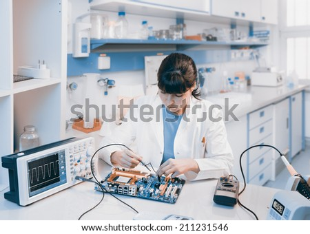 Young scientist repairs electronic device in modern laboratory - stock photo