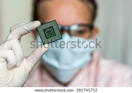 Young scientist showing the computer microchip before repairs electronic circuit - stock photo
