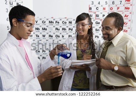 Young scientist with classmate and professor in classroom