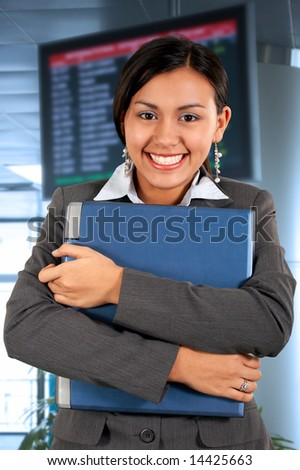 young secretary holding a laptop in an airport