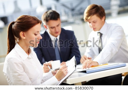 Young secretary keeping minutes of meeting