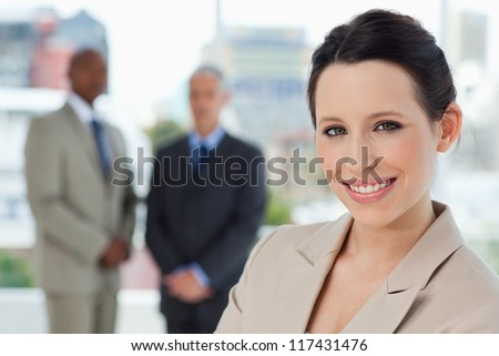 Young secretary standing upright in a relaxed way and showing a beaming smile - stock photo