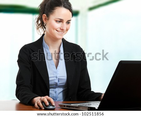 Young secretary typing on her laptop in the office