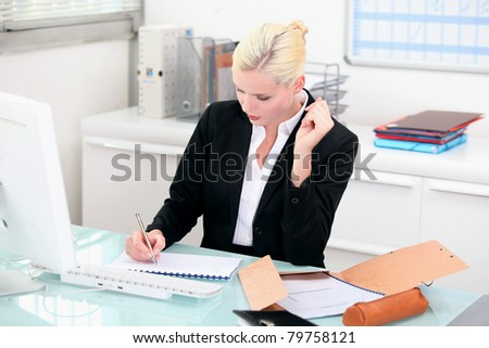 Young secretary writing on notebook - stock photo