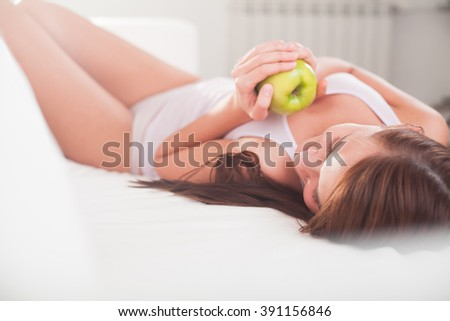 Young seductive brunette relax on a sofa - stock photo