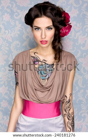 Young sensual attractive sexy european brunette girl with beautiful tattoo on her chest and arms posing for fashion photo shoot with red rose in her long hair in front of color floral background - stock photo