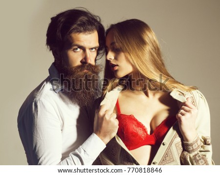Young sensual couple of bearded handsome man with beard and pretty sexy girl or beautiful woman in red sexi bra on grey wall