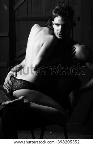 Young sensual couple of muscular macho man with bare torso and pretty sexy topless woman with back sitting on lover indoor on wooden background black and white, vertical picture - stock photo