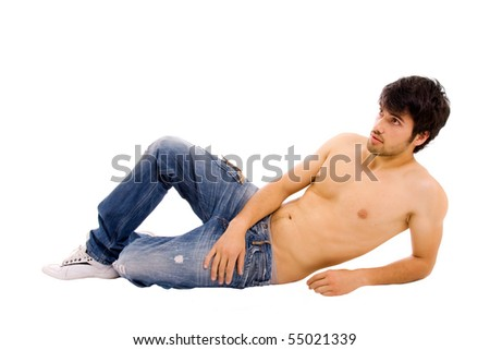 Young sensual man lying on the floor, studio shot
