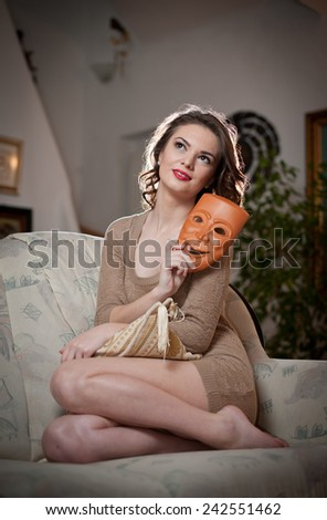 Young sensual woman sitting on sofa holding a mask. Beautiful long hair girl with comfortable clothes daydreaming on the couch. Attractive brunette wearing a tight fit short dress in cozy scenery - stock photo