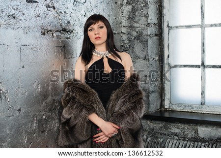 Young sensual woman standing by the window, looking rested and relaxed - stock photo