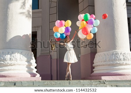Young sensual woman with colorful latex balloons keeping her dress, urban scene, outdoors - stock photo