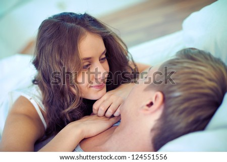 Young serene couple lying in bed - stock photo