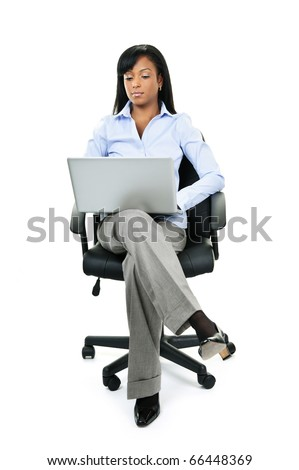 Young serious black woman sitting in leather office chair with laptop computer - stock photo
