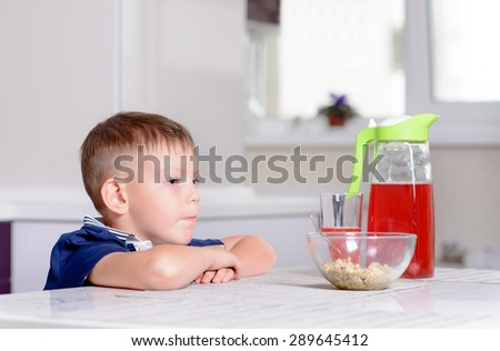 Young Serious Blond Boy Sitting at Kitchen Table Contemplating Bowl of Oatmeal Cereal and Red Juice at Breakfast - stock photo