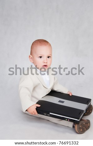 young serious boy in suit with computer