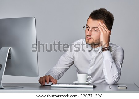 Young serious businessman is working  at his workplace on  gray background.