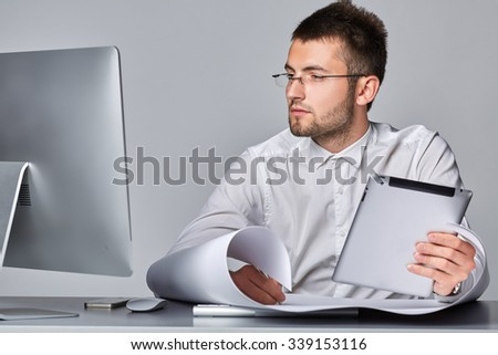 Young serious businessman is working with a sheet of whatman and  with the tablet in a hand at his workplace on  gray background.