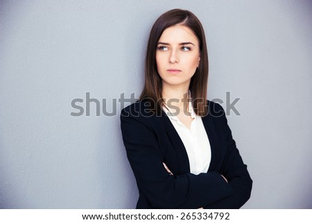 Young serious businesswoman with arms folded standing over gray background. Looking away - stock photo