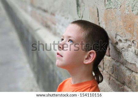 Young serious  cheerful Caucasian  boy beside a wall, selective focus  - stock photo