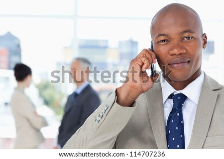 Young serious executive in a suit talking on the phone while his team stands behind him - stock photo