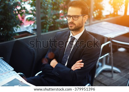 Young serious man employer in glasses waiting for start interview while sitting in comfortable restaurant interior, male confident CEO expects a partners to sign an agreement on further cooperation - stock photo