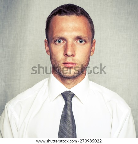 Young serious man in white shirt with tie over gray background. Closeup square studio portrait with vintage tonal correction old style instagram photo filter - stock photo