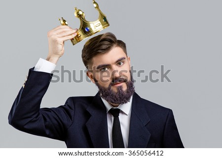 Young serious man, with violet beard and eyebrows, wearing in dark blue suit and tie, holding golden crown over his head, on white background, in studio, waist up