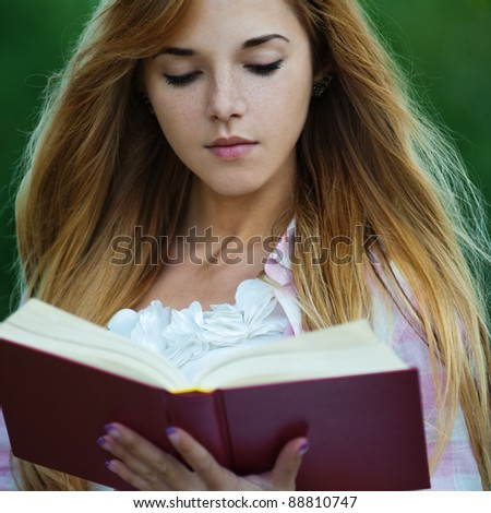 young serious woman park holding reading red book