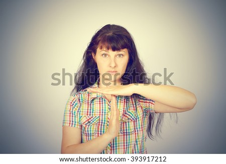 young serious woman showing time out gesture with hands, isolated gray background.  - stock photo