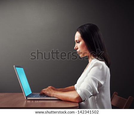 young serious woman working with laptop