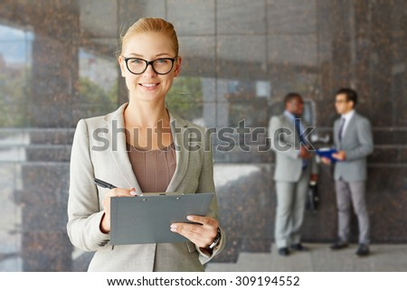 Young seriously looking businesswoman smiling at camera - stock photo